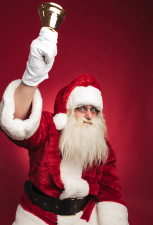 santa claus ringing his bell with hand in the air on red background
