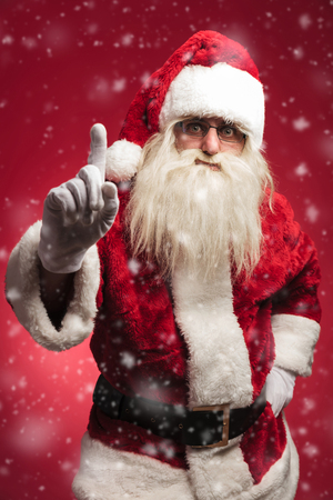 attention! santa claus is warning all the bad kids on red background Stock Photo