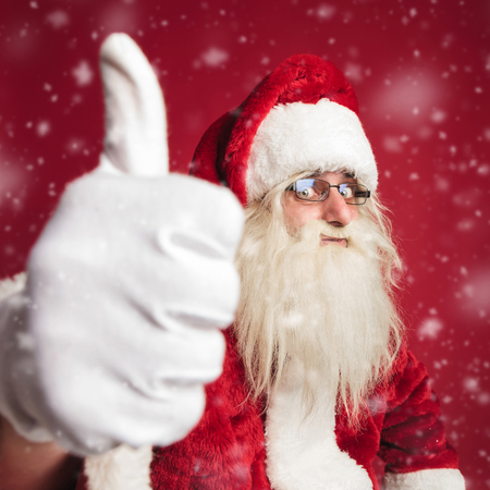 excited santa claus making the ok thumbs up hand sign on red background with snow falling Stock Photo