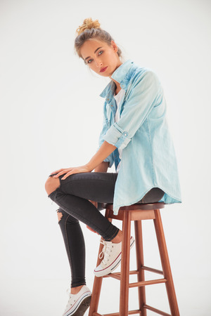 chairs: side view of a sexy casual woman sitting on a stool in studio