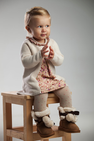 little seated girl is expecting to clap her hands while seated on grey background
