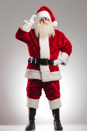 santa claus scratching his head and thinks on grey background