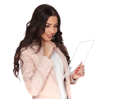 young happy woman reading on a futuristic tablet and thinks on white background Stock Photo