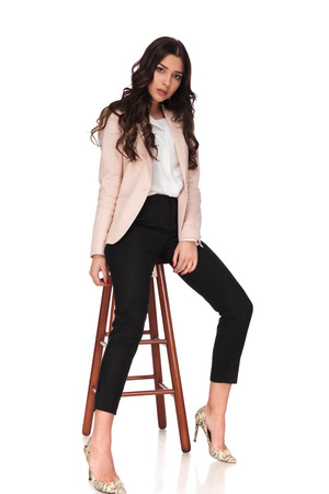 young fashion woman posing seated on a stool in studio, on white background