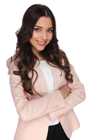 confident young business woman with hands crossed is smiling on white background