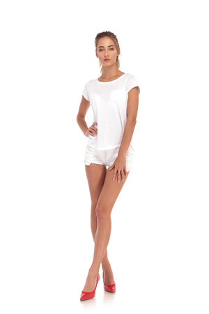 serious young casual woman in shorts posing on white studio background