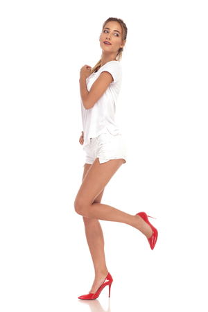 young woman walking and looking back over her shoulder on white background Stock Photo