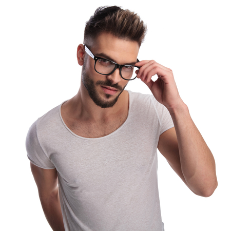 smiling casual man fixing his glasses on white background