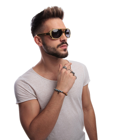 cool young casual man wearing sunglasses and looks to side on white background Stock Photo
