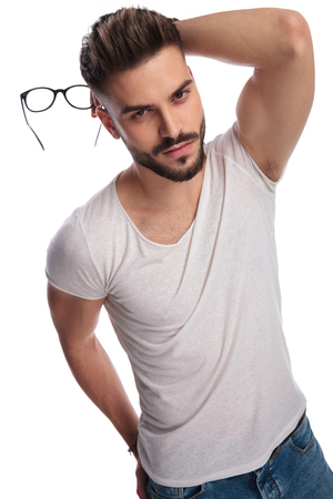 sexy casual man holding glasses in hand and behind head on white background