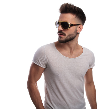 sexy young man in retro sunglasses looks to side onwhite background