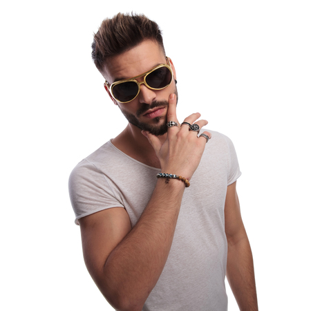 too cool for school young casual man holding hand on chin and wearing sunglasses on white background