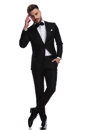 elegnat man in tuxedo making a military salute with finger on the temple of the head and smiles on white background