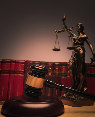 judge's gavel with justice statue and law books in the background Standard-Bild