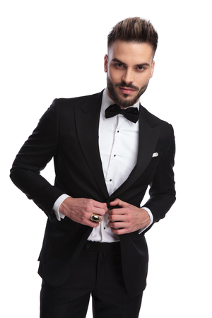 cool modern man in tuxedo holds button and looks at the camera on white background Stock Photo