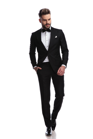 young fashion man in tuxedo walks and looks down on white background Archivio Fotografico