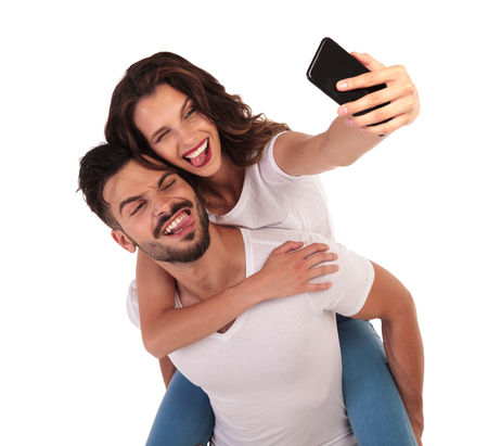happy couple having fun with their selfies , making stupid faces on white background