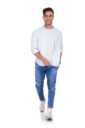 young casual man is smiling and walking on white background Stock Photo