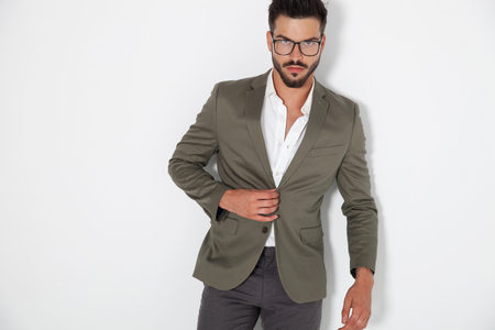 sexy elegant man buttoning his coat on looks to the camera on white background