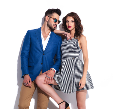 woman leans on man while they pose together on white background 스톡 콘텐츠