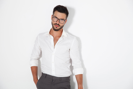 sexy young smart man standing with hand in pocket agaist white wall in studio Stock Photo