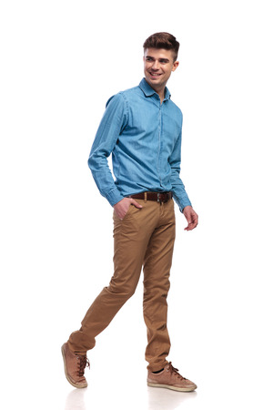 side view of a happy relaxed casual man walking on white background with on hand in his pocket