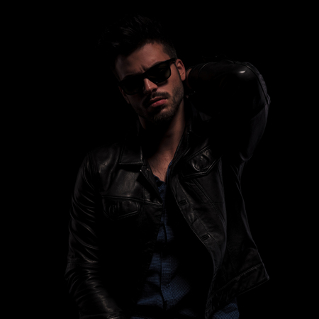 close up of provocative fashion man with sunglasses and leather jacket holding hand behind neck, on black background Stock Photo