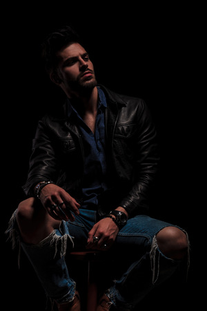 surprised seated fashion man in leather jacket  wearing rings and bracelets looks to side, on black background Foto de archivo - 97958064