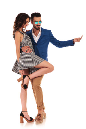 sexy man with sunglasses holding his laughing woman while snapping fingers on white background