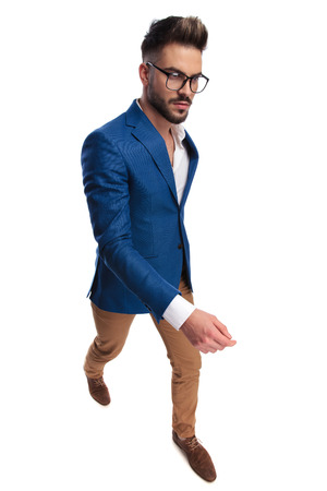 confident smart casual man walking to side on white background, full body picture Stock Photo