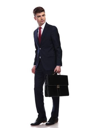 businessman with briefcase in hand looks to side while walking on a white background. He wears a navy suit and a red tie, full body picture.