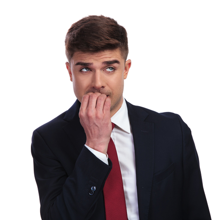 portrait of stressed businessman biting his nails and looking up to side while standing on white background. He wears a navy coloured suit and a red tie. Stok Fotoğraf