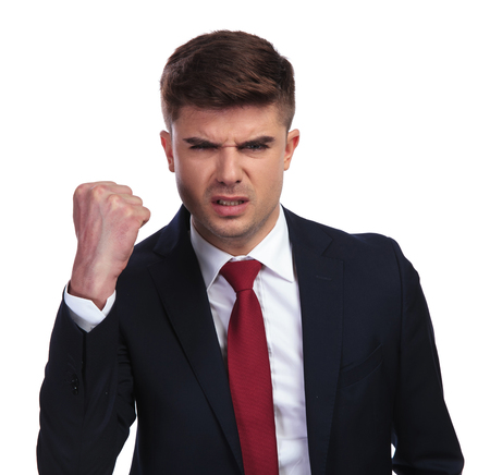 portrait of angry businessman shaking his fist on white background. He wears a navy coloured suit and a red tie.