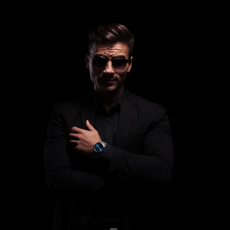 portrait of confident fashion man wearing black suit and sunglasses with arms crossed, standing on black background