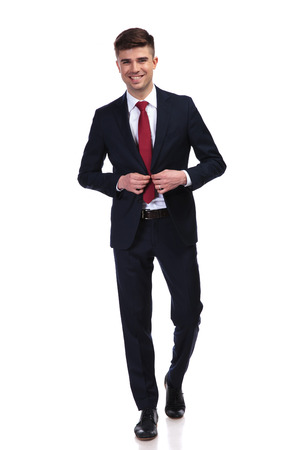 laughing businessman buttoning his navy suit and stepping forward while standing on white background, full body picture Stock Photo