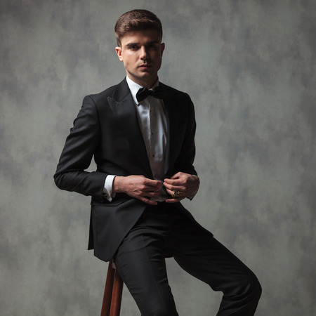 Sexy Businessman Dressed Formally Buttoning His Suit While Sitting