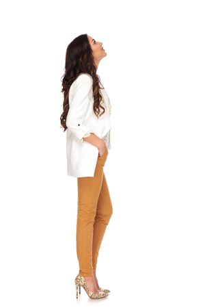 side view of relaxed businesswoman looking up at something while standing on white background with hands in pockets, waiting in line