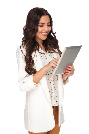 young and attractive businesswoman tapping on a tablet while standing on white background smiling