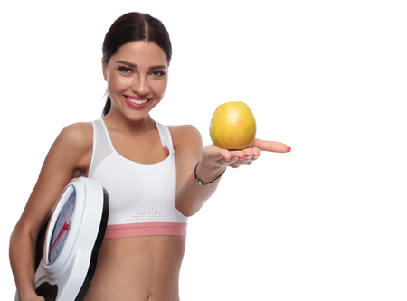 portrait of fit woman holding a scale offering you a golden apple while standing on white background