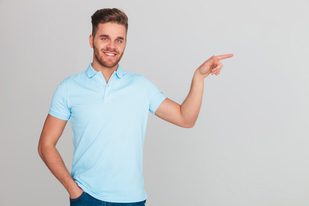 portrait of smiling relaxed man wearing a light blue polo t-shirt pointing to side while standing on light grey background Stock Photo