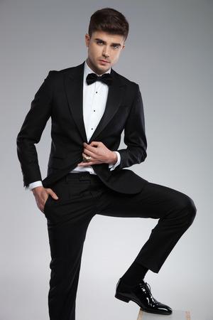 attraktiver junger Mann, der einen schwarzen Smoking trägt, der entspannt posiert, während er auf hellgrauem Hintergrund mit Bein steht, das auf Holzkiste und Hand in der Tasche ruht Standard-Bild