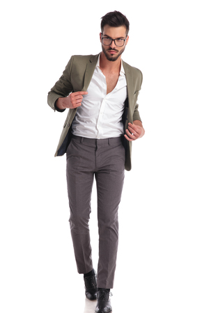 sexy elegant man with open collar and green suit walking forward on white background while holding the suit collar and looking to side
