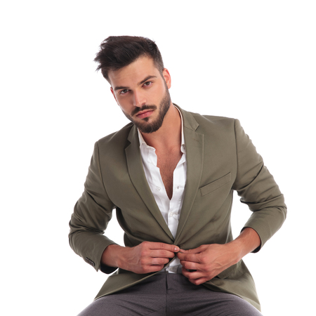 sexy young man with beard buttoning his green suit jacket while sitting on white background
