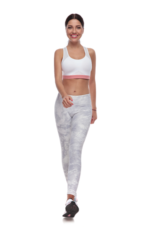 sexy fit woman walking forward to warm up for jogging on white background, full body picture. She is wearing a pair of white leggings and a white top.