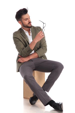 pensive stylish man with green suit sitting on wooden ladder on white background  looks at glasses while resting elbow in the other hand