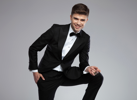 laughing businessman posing while leaning on his leg, standing on light grey background with hand in pocket, full body picture Stock Photo
