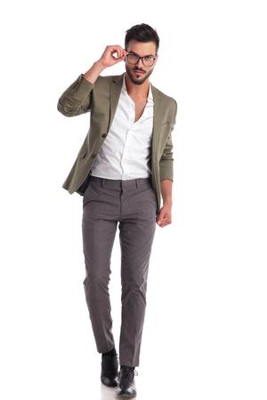smart stylish man wearing green suit walking on white background while fixing glasses