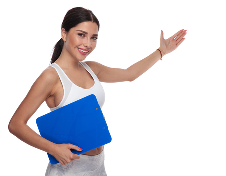 sexy fit woman welcomes you to join her gym with a hand gesture while holding a blue clipboard. She is standing on white background, wearing a white top, portrait picture