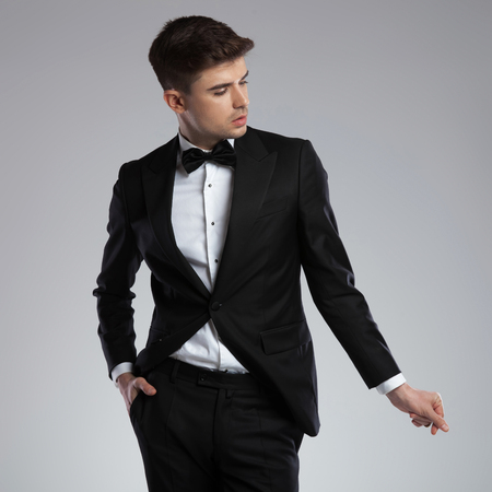 portrait of sexy man dressed formally snapping his fingers and looking to side while standing on light grey background with hand in pocket, looking relaxed
