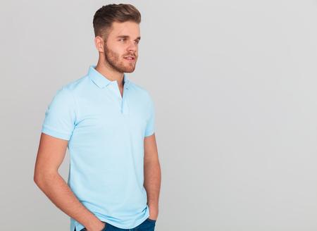 Ritratto di uomo rilassato che indossa la maglietta polo azzurra che guarda al lato mentre si trova su sfondo grigio chiaro con le mani in tasca